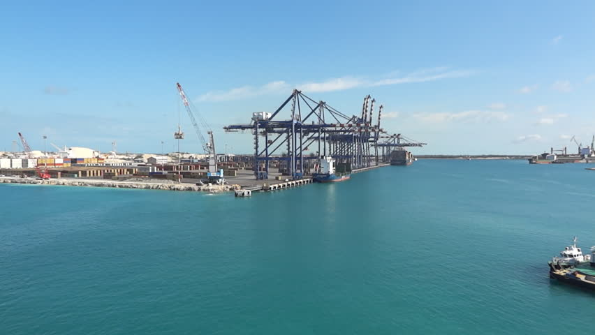 A timelapse shot of cranes loading a cargo ship at the Freeport shipping yard in the Bahamas with a clear blue sky and the beautiful water of the Caribbean Ocean on a warm tropical day.