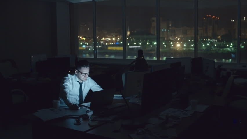 Tired sleepy man sitting at desk in dark office at night and working on laptop, drinking coffee and trying to concentrate, wide shot on Sony NEX700 + Odyssey 7Q | Shutterstock HD Video #18171358