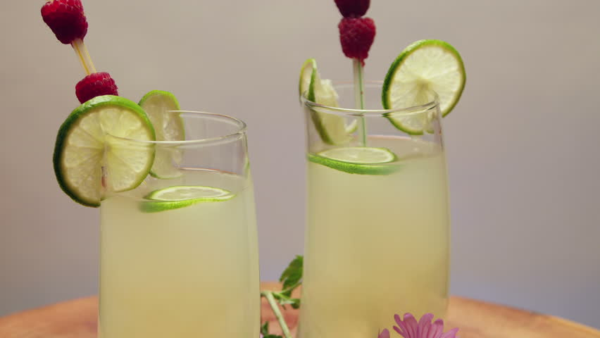 Two glasses of lemonade with lime and raspberry, rotating