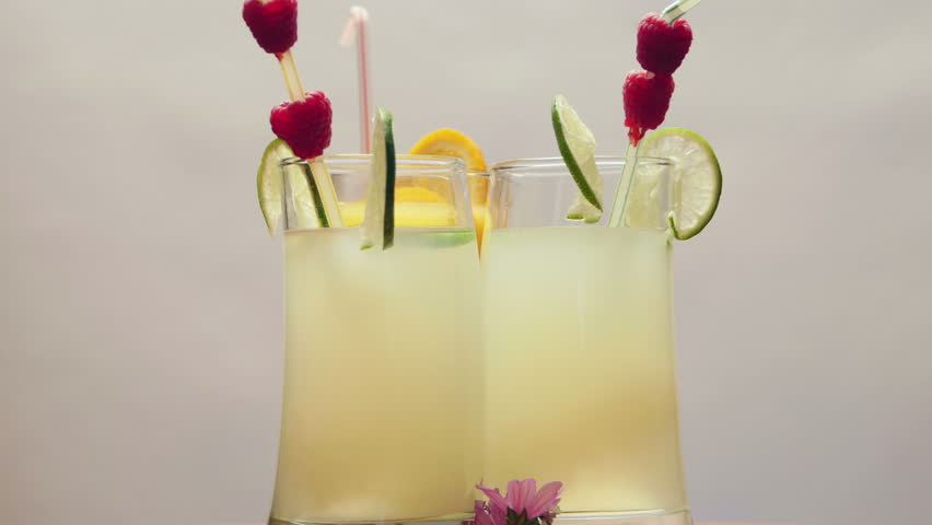 One glass of natural orange juice and two glasses of lemonade, rotating