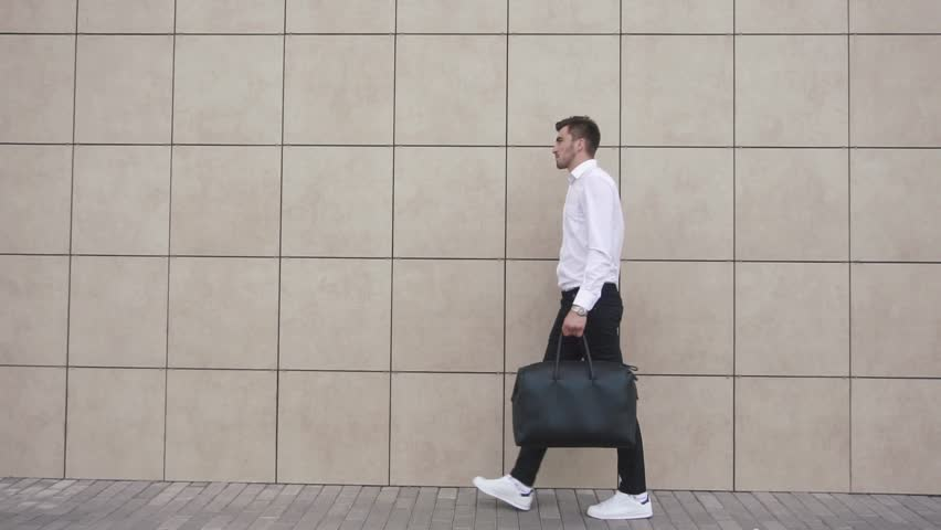 Young confident businessman walking on the background of the office. The modern businessman concept.