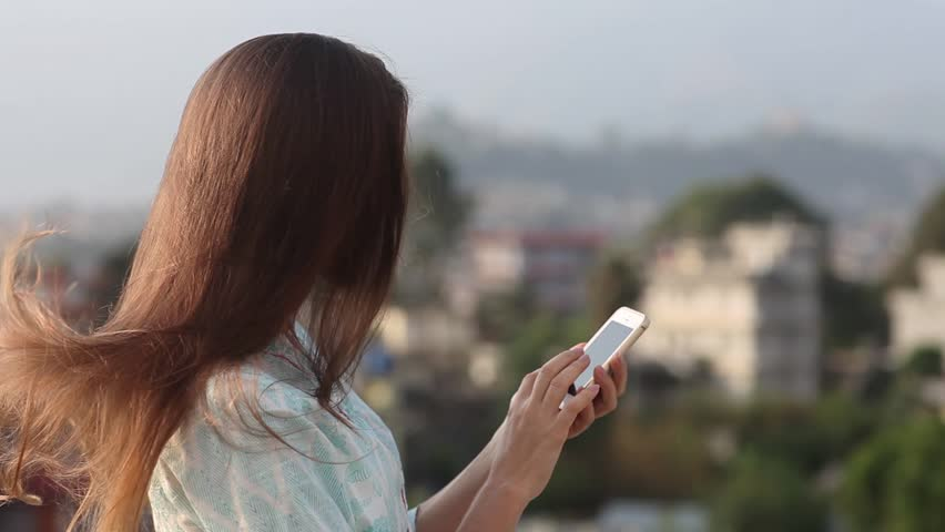 Beautiful Young Professional Woman Dials a Phone Number on the Roof of the Office Balcony in the City During the Day. it Stands on the Belt Look Away From the Camera, Her Hair Developing on a Wind.