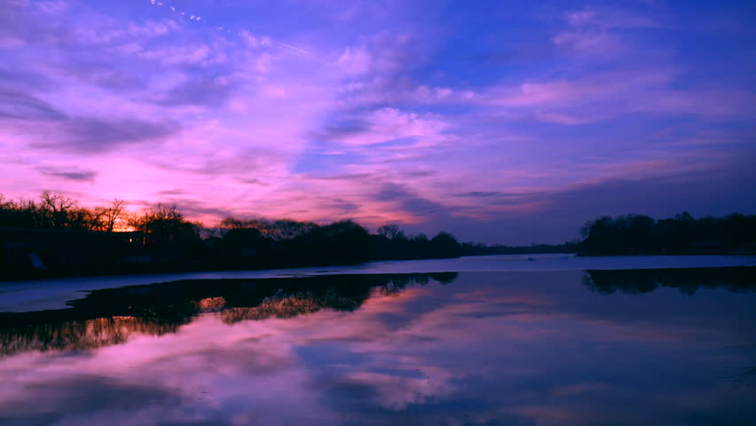 Spectacular colorful and dynamic sunset over the lake. Fast moving and evolving clouds are going towards the camera.