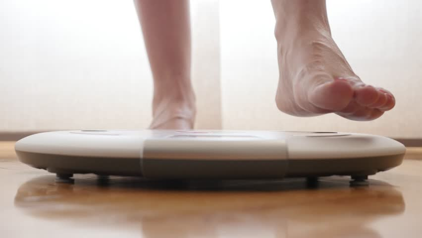 Pedicured bare feet female measuring weight on health scale 4K 2160p 30fps UltraHD footage - Close-up woman legs approaching to weighing digital instrument 3840X2160 UHD video