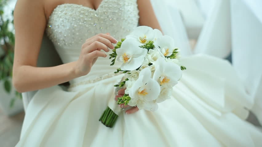 Beautiful bride is holding white wedding bouquet. Bridal accessories. Details for marriage