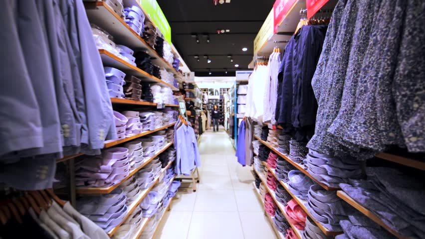 HONG KONG, CHINA - APRIL 2, 2016: Walking along the shelves with clothes in Uniqlo store in Hong Kong mall. It's a Japanese casual wear designer of the latest essentials for women, men, kids & babies