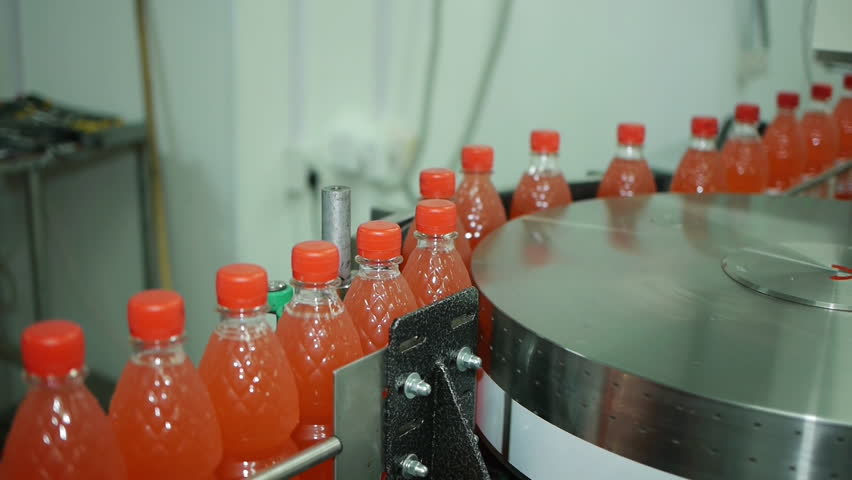 bottle of soda move in automatic production line conveyor twisted and glued labels