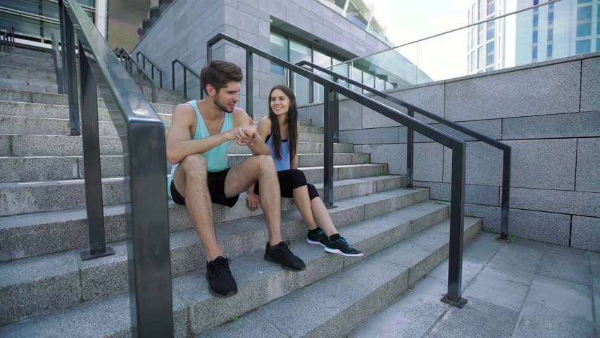 Healthy man and woman having a rest after morning training, sitting and talking on stairs at modern stadium | Shutterstock HD Video #18280384