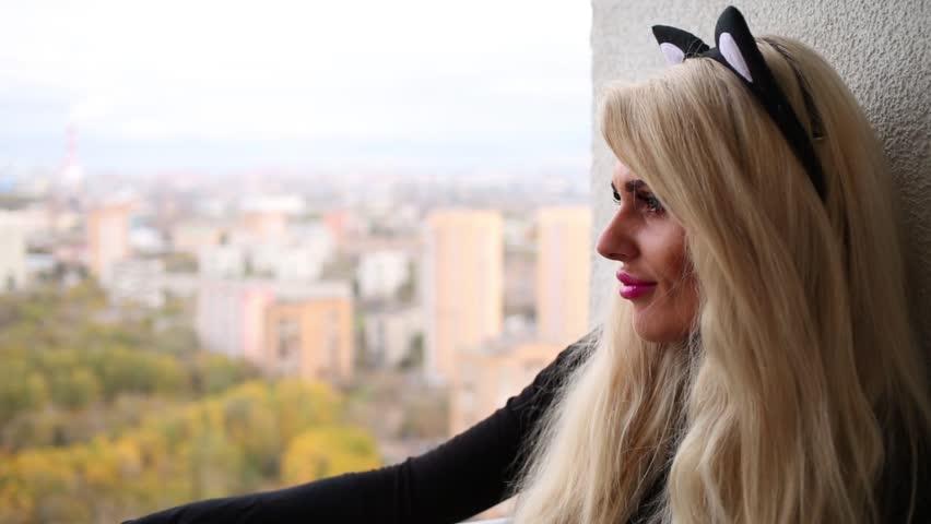 Beauty woman with a black cats ears is sitting near wall. | Shutterstock HD Video #18337453