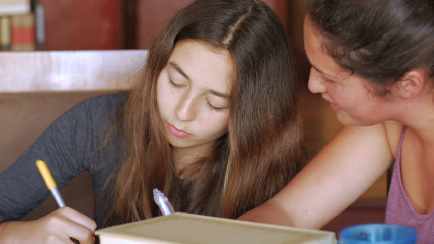 Push in of two teenager girls studying together and having a good time in their house doing homework