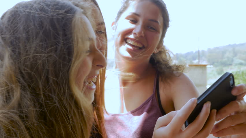 Three teenage girls take a selfie outside and share it with each other on their smart phone while having a good time.