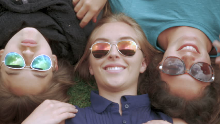 Three beautiful teenage girls lying on the grass take off and put on their sunglasses while laughing and smiling