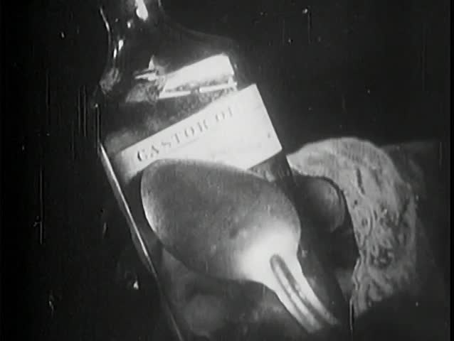 Close-up of spoon pointing to castor oil label on bottle