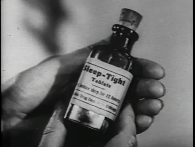 Close-up of hands opening bottle of sleeping pills