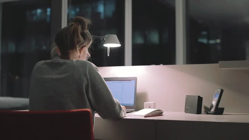 Young concentrated woman, sitting in her room or office with french windows in the dark at the lamp.Studies late at night.Staying up late. Overworking. Working late on laptop.       Shutterstock HD Video #18499183