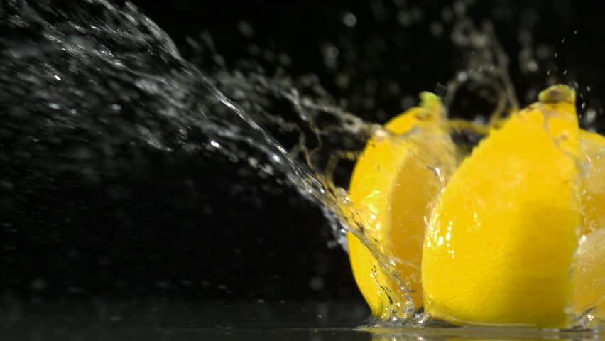 Slo-motion lemon  falling into wedges against black drop #1881007