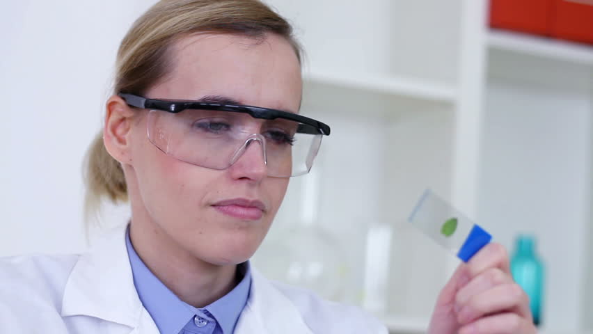 Female scientist with magnifying glass looking at glass slide with green leaf - HD stock video clip