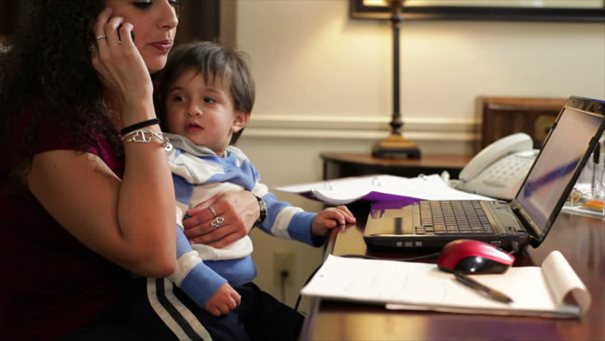 A pretty Hispanic work-at-home mom holds her son while taking a phone call and making notes on a writing table. - HD stock footage clip