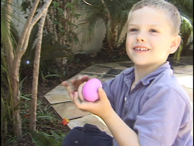 A young boy hunts for Easter eggs. - SD stock footage clip