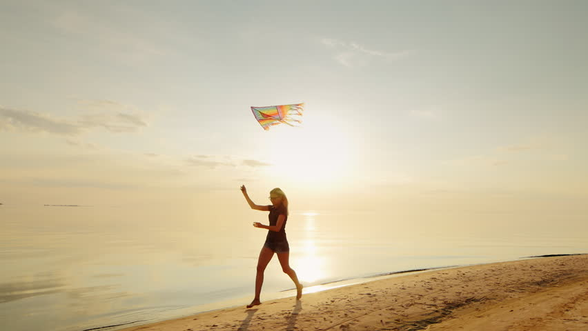 Happy young woman running with a kite. Concept - cloudless prospects, confidence and carelessness | Shutterstock HD Video #18964762