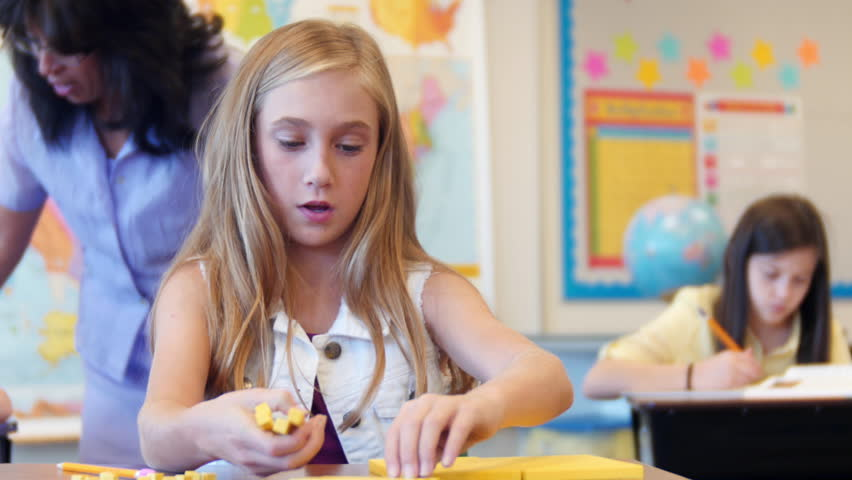 A young girl is using base ten blocks for place value. Then she looks up and smiles.   Shutterstock HD Video #19007755