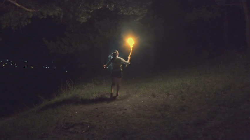 Brave girl traveling the night forest holding a fiery torch in hand. Slow motion. | Shutterstock HD Video #19052971