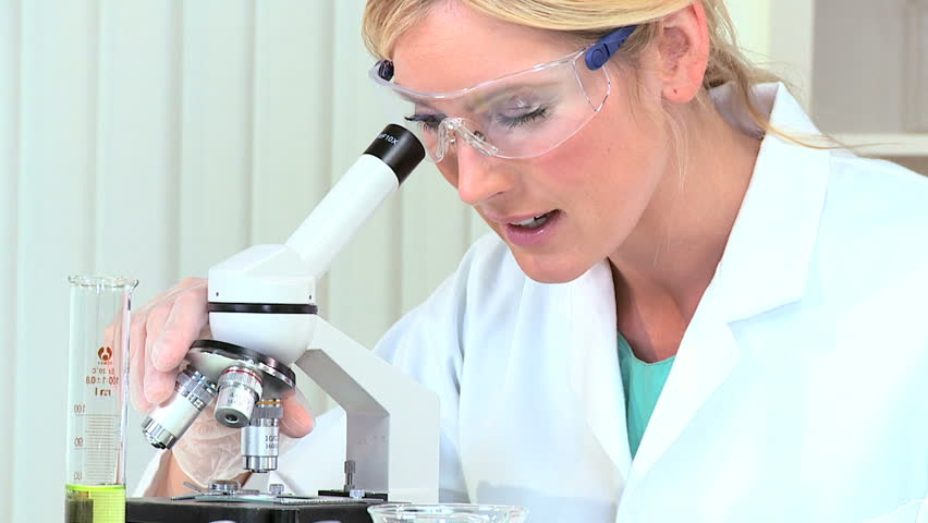 Female laboratory assistant working with microscope and test tubes - HD stock footage clip