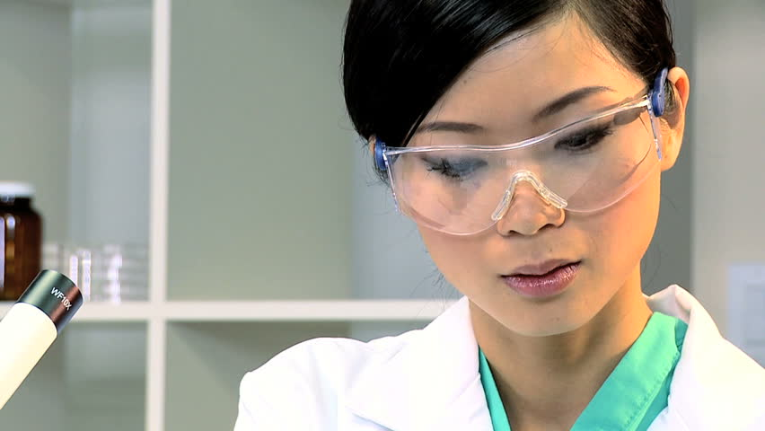 Female student doctor working with a microscope and test tubes in laboratory-full face - HD stock footage clip