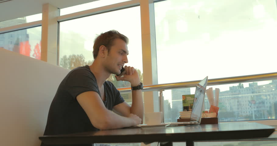 A young business man speaking on the phone sitting in a cafe and viewing e-mail on a laptop. in slow motion. zoom camera | Shutterstock HD Video #19107367