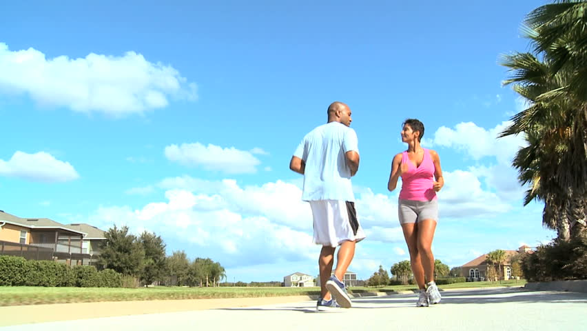 Young ethnic female jogging with personal trainer - HD stock footage clip