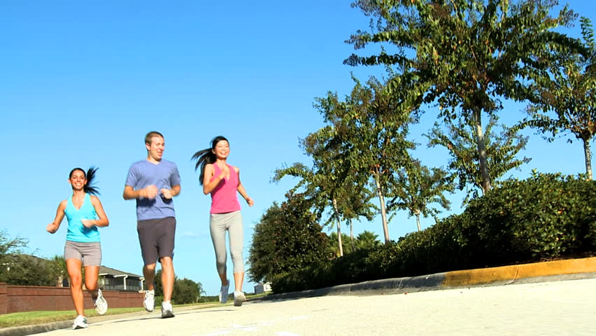 Young running partners friends keeping fit together jogging outdoors on suburban roads - HD stock footage clip