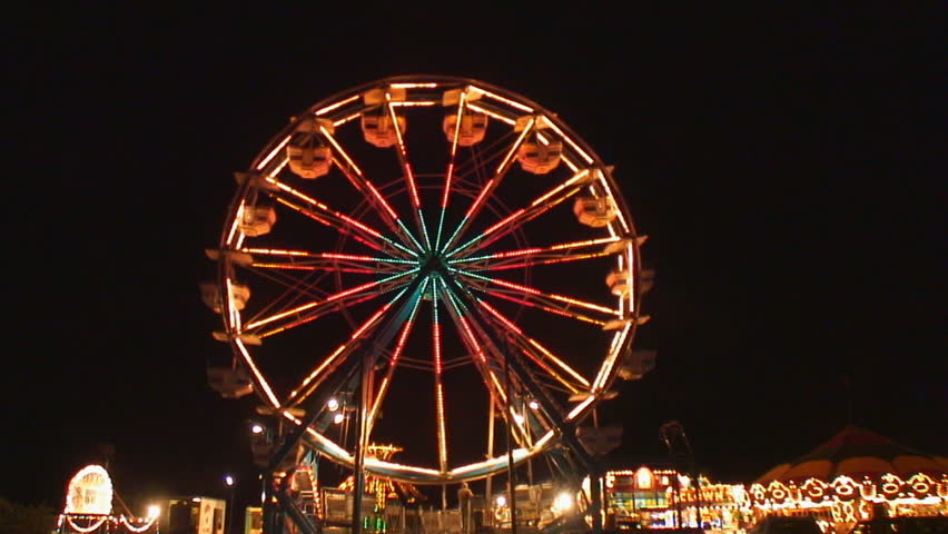 Ferris wheel lights sparkle brightly as it slows to add passengers - HD stock footage clip