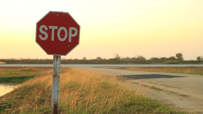 Stop sign at airfield during sunset