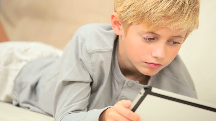 Young Blonde Boy Using A Modern Wireless Tablet On Home