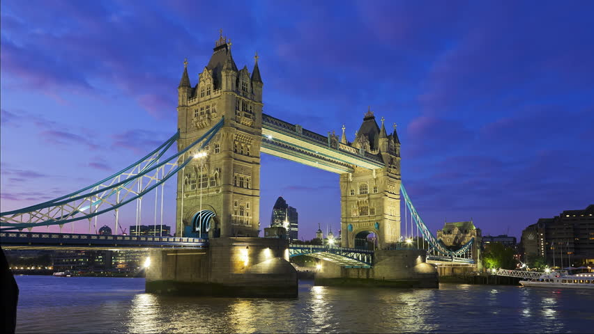 Tower Bridge in London at night being open  for passing underneath boat, London, United Kingdom. Time lapse footage of boat on Thames River with City of London lights in the background.