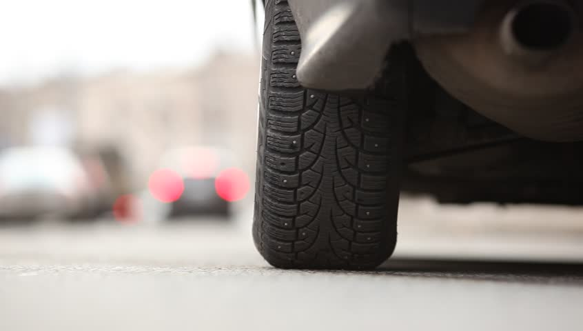 Rear tyre of starting car, vehicle begin to move, environment road noise. Low camera position, studded tire of standing car. Left rear wheel view, auto ride away, rendered in blur at distance.