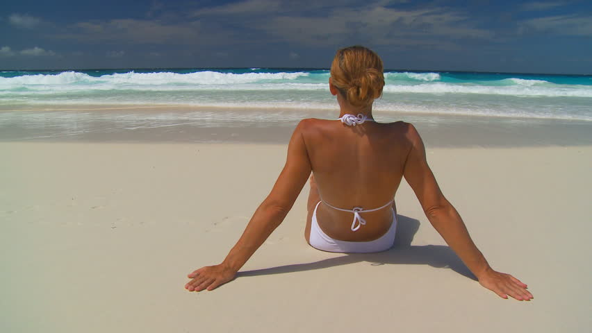 backview of young woman sitting on sandy beach