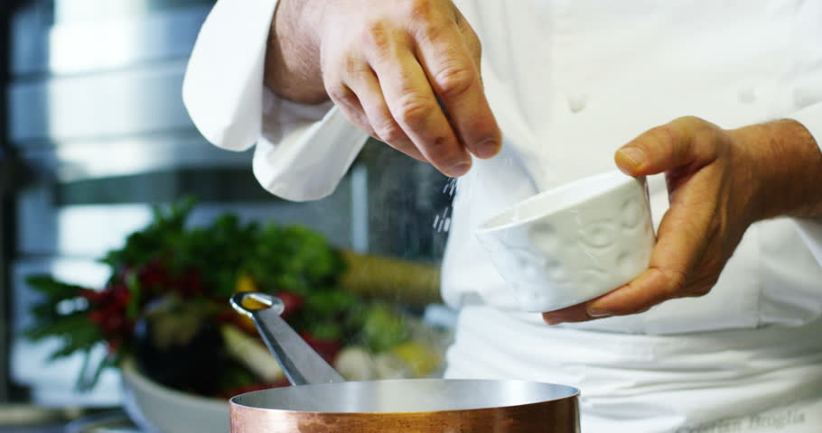 in an Italian professional kitchen a chef pours salt on a dish or in the water to boil the Italian pasta concept of healthy and light food. bio