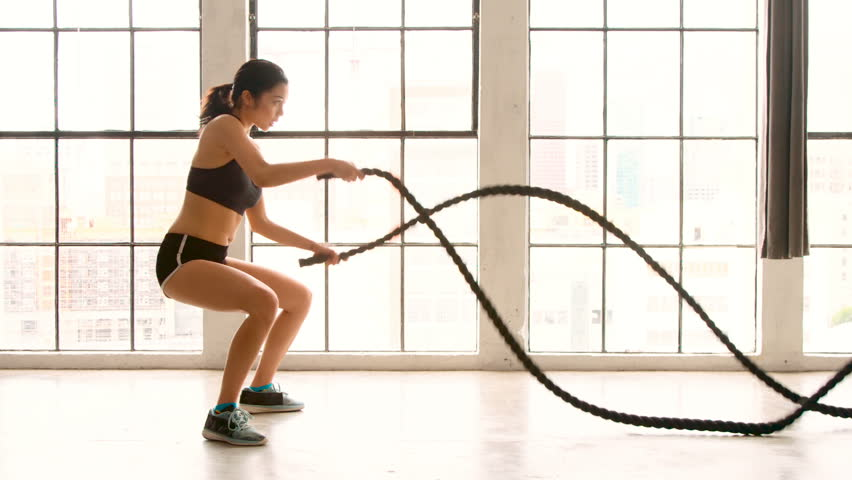 Athletic Female Working Out Using Battle Ropes. High-intensity interval training. Slow Motion.