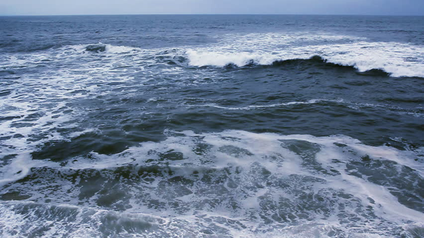 Slow motion waves breaking near a rocky shore - quality HD footage captured at 60fps.