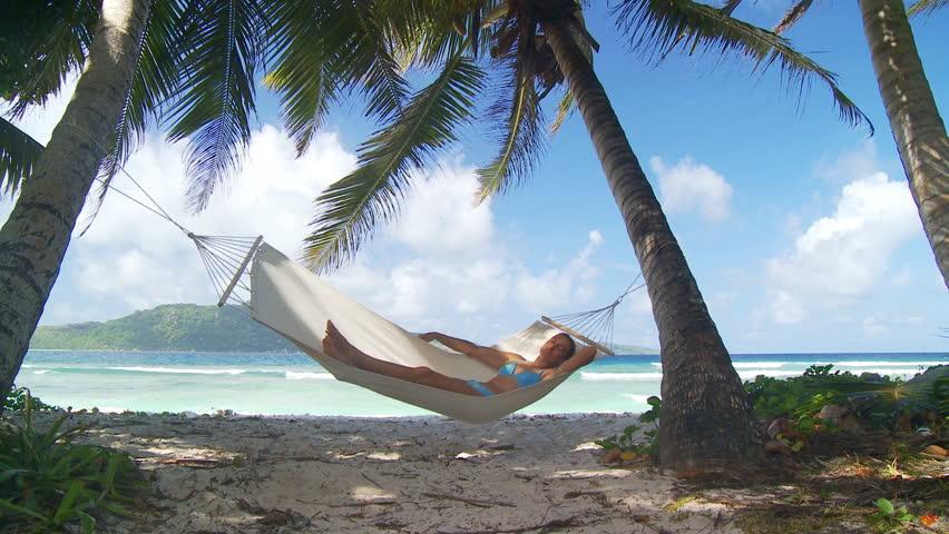 young woman in bikini enjoying her nap in hammock in the shade of palmtrees on tropical beach