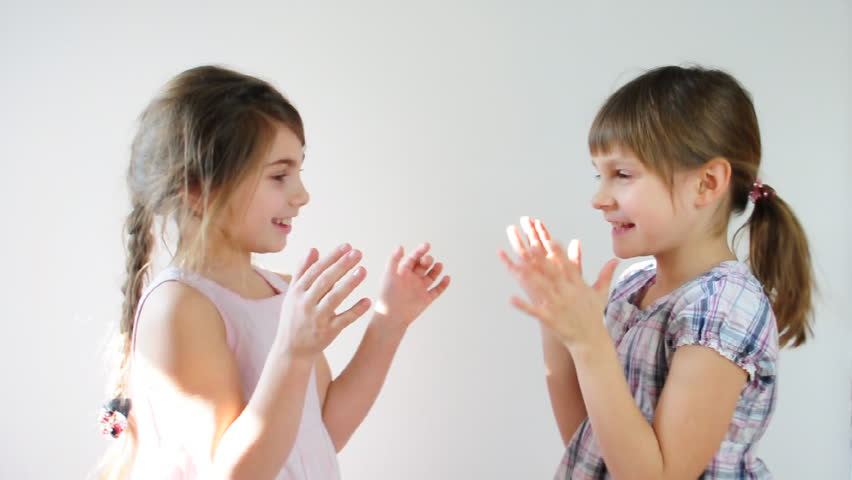 Two happy playful children laughing and playing pat-a-cake - HD stock video clip