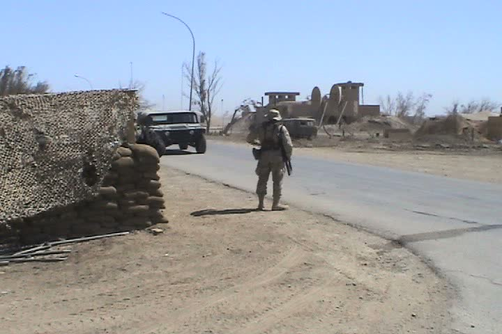 IRAQ - CIRCA MAY 2003: Checkpoint at Talil, mileage signs on post to Wrigley Field and Atlanta, soldier holding weapon in back of humvee with Baghdad Mosque in Background. - SD stock footage clip