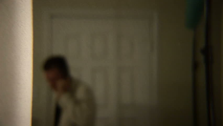 Man walks in his house talking on the phone NOTE: shot with 35mm adapter to get shallow DOF - HD stock footage clip