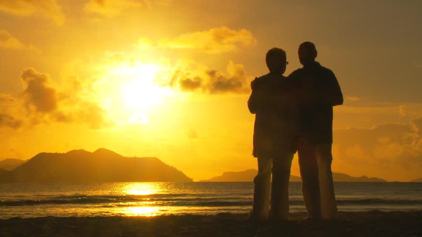 elderly couple cheering on beach at sunset