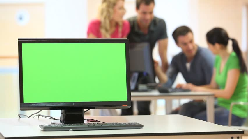 Green desktop screen set in front of workgroup - HD stock footage clip