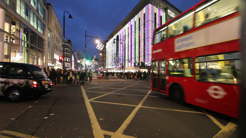 LONDON, UK - DECEMBER 27: Busses and other traffic drive beneath Christmas lights on Oxford Street on December 27, 2011 in London, UK. Oxford Street is one of the main shopping streets of London. - HD stock footage clip