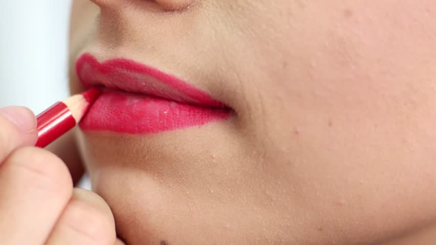 Female lips red lip pencil drawing the contour of the lips before applying lipstick, make-up artist doing make-up girl in a beauty salon. Girl paints her lips red lipstick, make-up artist doing make | Shutterstock HD Video #19855213