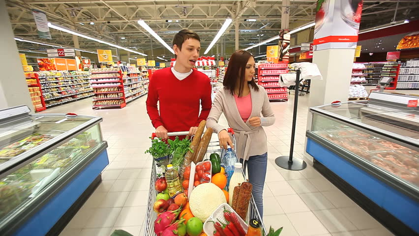 Cheerful couple walking through mall with a market trolley full of products
