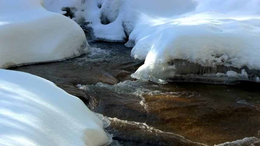 A beautiful crystal clear river flows at Diane's bath in Bartlett, New Hampshire.  The moving water forms interesting shapes as it carves a path through the pristine ice and snow of winter. - HD stock video clip